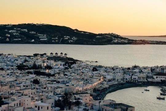 what to do in Mykonos: Mykonos is famous for its nightlife. Watching the sunset from the iconic 180 Degrees Sunset Bar is one of the top things to do in Mykonos. Grab some cocktails and watch the sun to go down in a renowned 180 Degrees Sunset Bar