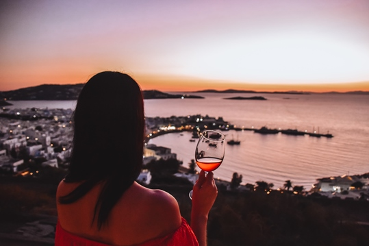 what to do in Mykonos: watching the sunset in Mykonos is a must thing what you need to do in Mykonos. Greece is well-known for its beautiful sunsets. Sipping wine in a bar and watching sunset is an experience not to be missed when in Mykonos.