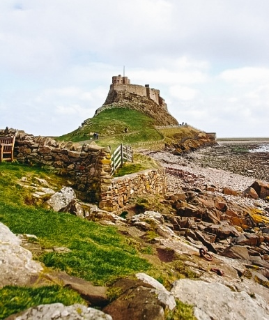 castles in England: Lindisfarne Castle is one of the most famous castles in England because it has a long history dating back thousands of years. Vikings and later Scots made this border area between Scotland and England vulnerable to attacks. Later, there has been a monastery that Henry VIII destroyed during the Reformation. The fortress is also famous because it gets cut off from the mainland when the tide rolls.